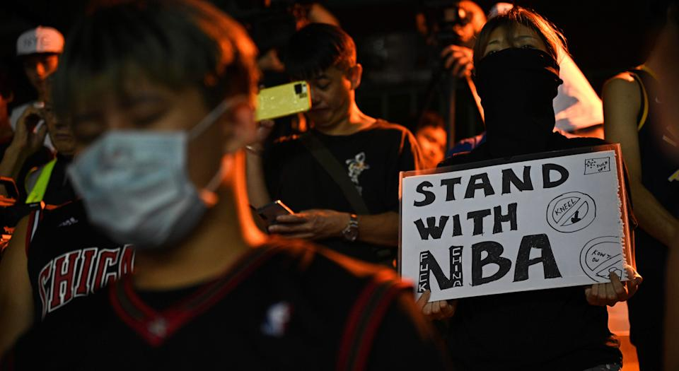 """A protester holds a sign at the Southorn Playground in Hong Kong on October 15, 2019, during a rally in support of NBA basketball Rockets general manager Daryl Morey and against comments made by Lakers superstar LeBron James. - US basketball superstar LeBron James on October 14, 2019, has sharply criticised a Houston Rockets executive for angering China with a tweet supporting protesters in Hong Kong, saying the executive was """"misinformed"""" and should have kept his mouth shut. (Photo by Anthony WALLACE / AFP) (Photo by ANTHONY WALLACE/AFP via Getty Images)"""