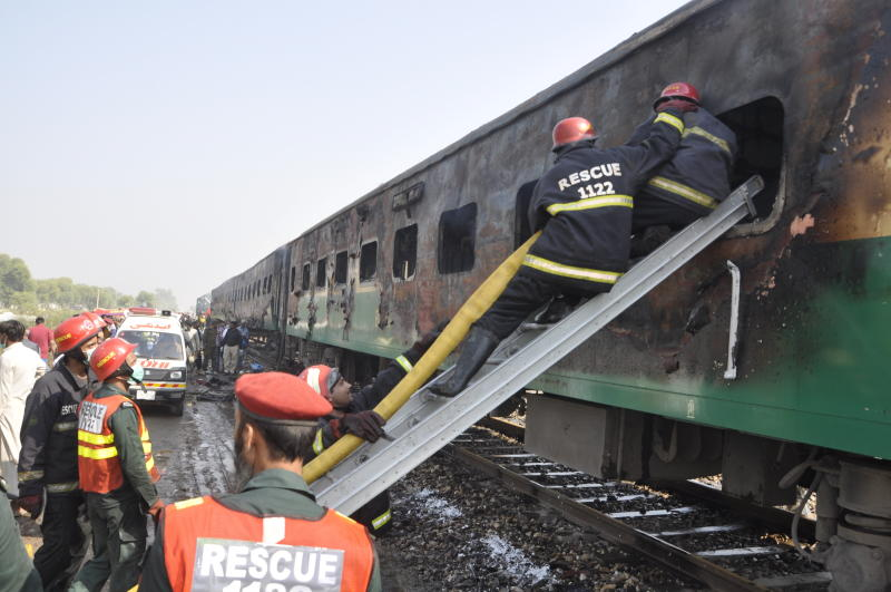 Rescue workers look for survivors following a train damaged by a fire in Liaquatpur, Pakistan, Thursday, Oct. 31, 2019. A massive fire engulfed three carriages of the train traveling in the country's eastern Punjab province (AP Photo/Siddique Baluch)