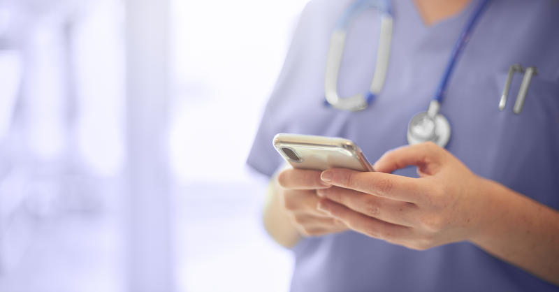 Female surgeon texting on mobile phone in hospital or surgery. She is wearing scrubs and has her stethoscope around her neck