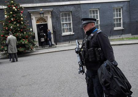 An armed police officer walks past 10 Downing Street, London, Britain, December 6, 2017. REUTERS/Toby Melville