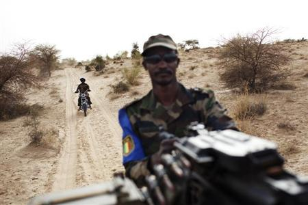 A Malian soldier holds a machine gun mounted on a pick-up truck during a military escort outside Timbuktu