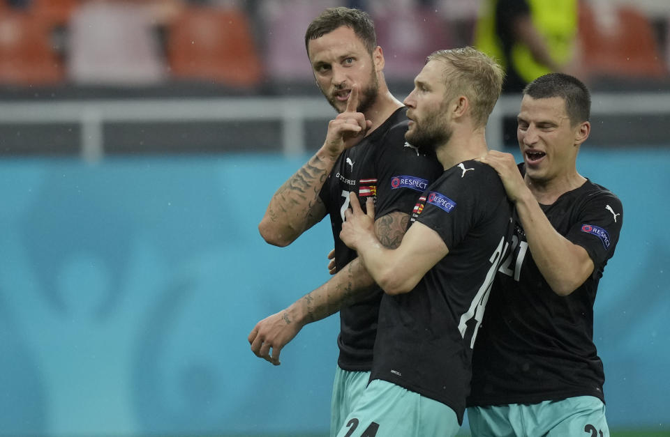 Austria's Marko Arnautovic, left, celebrates with teammates after scoring his side's third goal during the Euro 2020 soccer championship group C match between Austria and Northern Macedonia at the National Arena stadium in Bucharest, Romania, Sunday, June 13, 2021. (AP Photo/Vadim Ghirda, Pool)