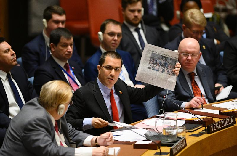 Venezuelan Foreign Minister Jorge Arreaza (C) shows a newspaper as he speaks to a United Nations Security Council meeting on the situation in Venezuela on January 26, 2019