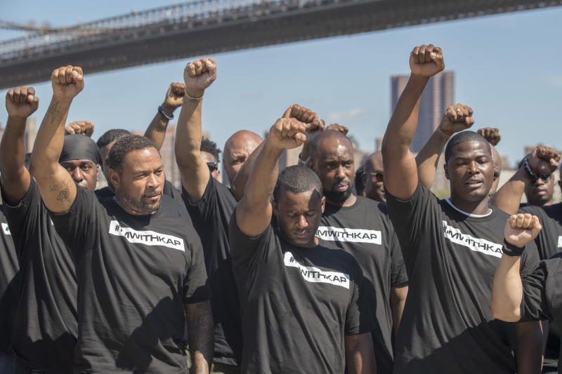 Members of law enforcement raise their fists during a rally in New York to show support for Colin Kaepernick. (AP)