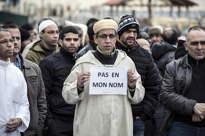 """A Muslim man holds a sign reading """"Not in my name"""", during a gathering on January 9, 2015 near the mosque of Saint-Etienne, eastern France, after the attack on the offices of weekly satirical Charlie Hebdo (AFP Photo/Jean-Philippe Ksiazek)"""