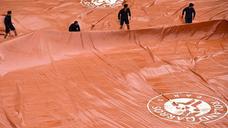 Groundstaff members pull covers across the court surface as rain falls. (Photo by MARTIN BUREAU/AFP/Getty Images)