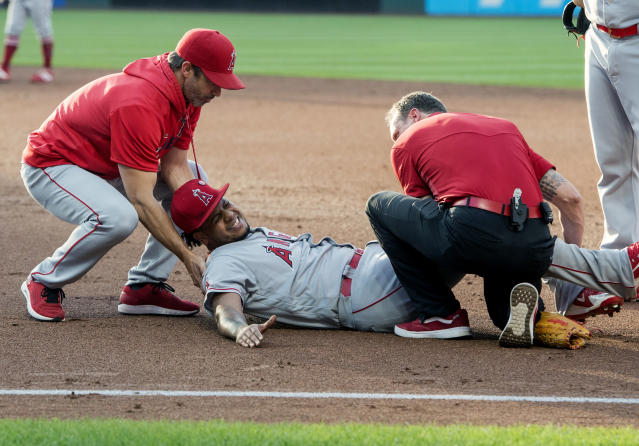 Los Angeles Angels starting pitcher Felix Pena, center, is tended to by trainers after an injury while covering first base during the second inning of a baseball game against the Cleveland Indians in Cleveland, Saturday, Aug. 3, 2019. (AP Photo/Phil Long)