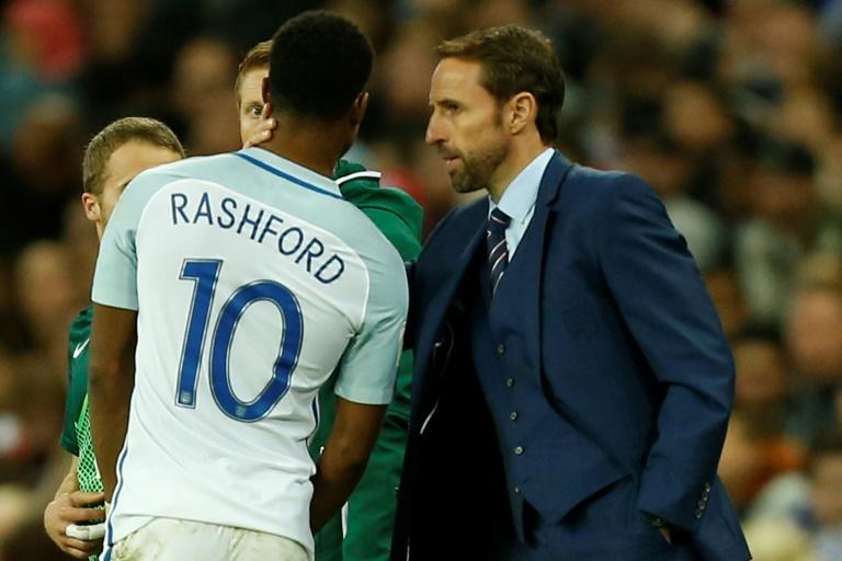 England's manager Gareth Southgate talks to striker Marcus Rashford on the touchline during their FIFA 2018 World Cup qualifier match against Slovenia, at Wembley Stadium in London, on October 5, 2017