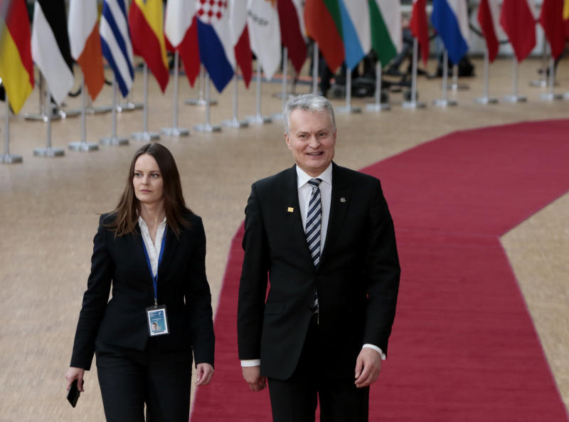 Lithuanian President Gitanas Nauseda, right, arrives for an EU summit at the European Council building in Brussels, Thursday, Feb. 20, 2020. After almost two years of sparring, the EU will be discussing the bloc's budget to work out Europe's spending plans for the next seven years. (AP Photo/Virginia Mayo)