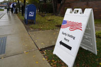 An information sign shows outside the Elk Grove Village Hall as voters wait in line during early voting at Elk Grove Village, Ill., Friday, Oct. 23, 2020. The US early voting total in 2020 has already exceeded the number of early votes cast in 2016 and there are still 11 more days to go until Election Day. (AP Photo/Nam Y. Huh)