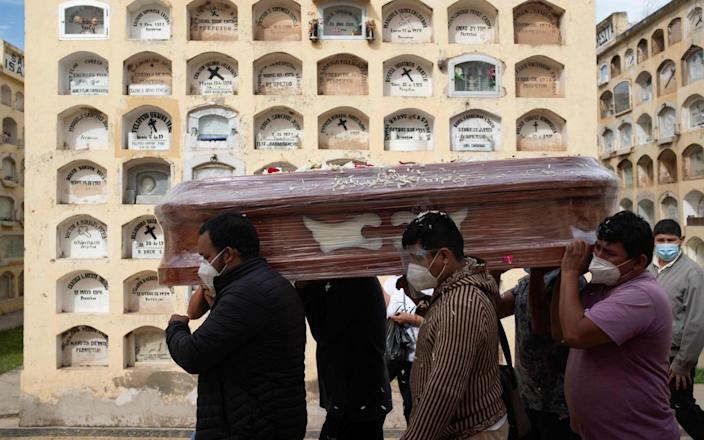 Relatives of a Covid-19 victim carry a coffin at the General Cemetery in the central city of Huanuco - OSCAR ROSARIO/AFP