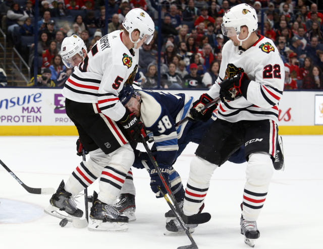 Columbus Blue Jackets forward Boone Jenner, center, collides with Chicago Blackhawks defenseman Connor Murphy, left, as Blackhawks forward Ryan Carpenter defends during the second period of an NHL hockey game in Columbus, Ohio, Sunday, Dec. 29, 2019. (AP Photo/Paul Vernon)
