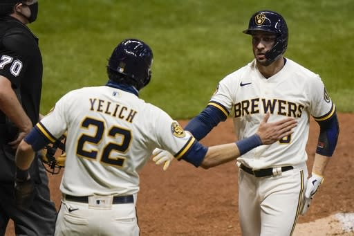 Milwaukee Brewers' Christian Yelich and Ryan Braun celebrate after scoring on a hit by Daniel Vogelbach during the third inning of a baseball game against the St. Louis Cardinals Tuesday, Sept. 15, 2020, in Milwaukee. (AP Photo/Morry Gash)