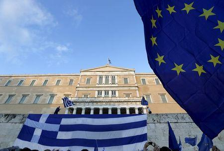 Protesters wave a Greek flag (L) at the entrance of the parliament building during a rally calling on the government to clinch a deal with its international creditors and secure Greece's future in the Eurozone, in Athens, Greece, June 22, 2015.  REUTERS/Yannis Behrakis