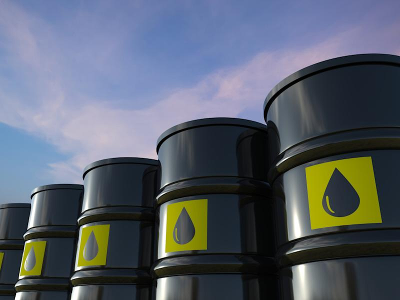 Black crude oil barrels lined up in a row.