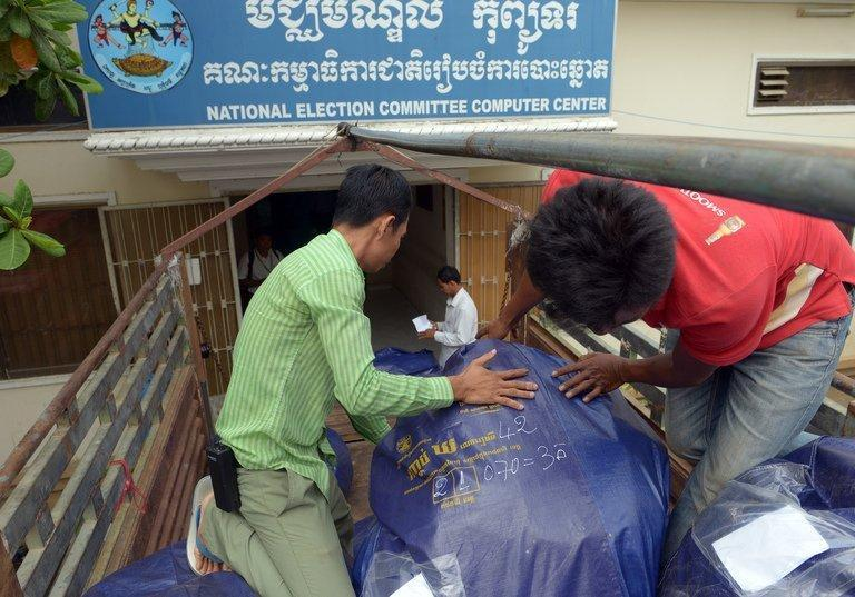 Cambodian National Election Committee officers pull a bag of used ballots from a truck in Phnom Penh on August 3, 2013. Cambodia's opposition party has agreed to work with the government to probe alleged election fraud, the party said Saturday, in an apparent step towards ending a political impasse since last week's disputed poll