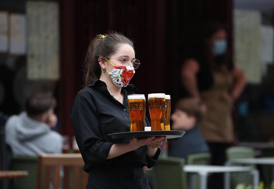 A server carries a tray of drinks from a pub in the Grassmarket in Edinburgh, as beer gardens, non-essential shops, restaurants and cafes, along with swimming pools, libraries and museums in Scotland reopen today after lockdown restrictions have eased. Picture date: Monday April 26, 2021. (Photo by Andrew Milligan/PA Images via Getty Images)