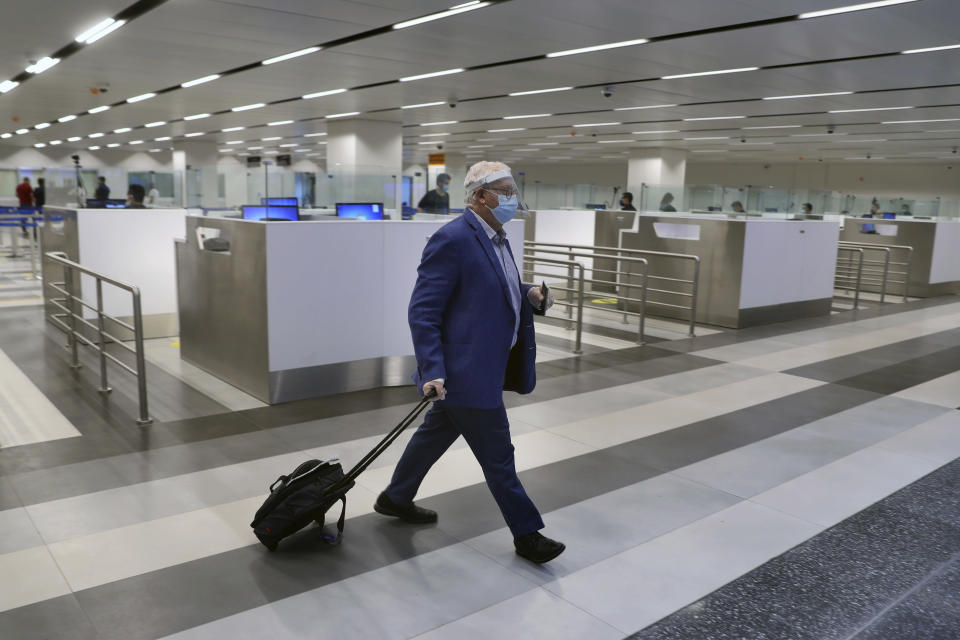 A passenger arrives at the Rafik Hariri International Airport in Beirut, Lebanon, Wednesday, July 1, 2020. Beirut's airport is partially reopening after a three-month shutdown and Lebanon's cash-strapped government is hoping that thousands of Lebanese expatriates will return for the summer, injecting dollars into the country's sinking economy. (AP Photo/Bilal Hussein)