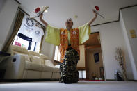 """Olympic fan Kyoko Ishikawa shows her cheering at her home Saturday, April 10, 2021, in Tokyo. Ishikawa, president of an IT company, has attended every Summer Olympics since Barcelona in 1992, becoming famous as an unofficial """"International Olympic Cheerleader."""" She relishes joining in with fans from everywhere to cheer for their athletes. (AP Photo/Eugene Hoshiko)"""