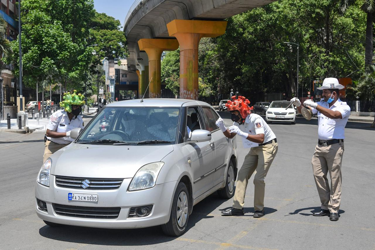 Traffic police personnel (L and C) wearing coronavirus-themed helmets participate in a campaign to educate the public during a government-imposed nationwide lockdown as a preventive measure against the COVID-19 coronavirus in Bangalore on March 31, 2020. (Photo by Manjunath Kiran / AFP) (Photo by MANJUNATH KIRAN/AFP via Getty Images)