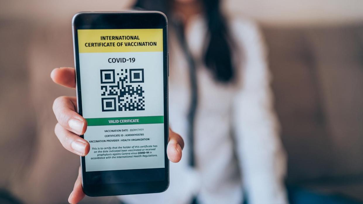 A woman presents a smartphone with a valid digital international vaccination certificate for COVID-19