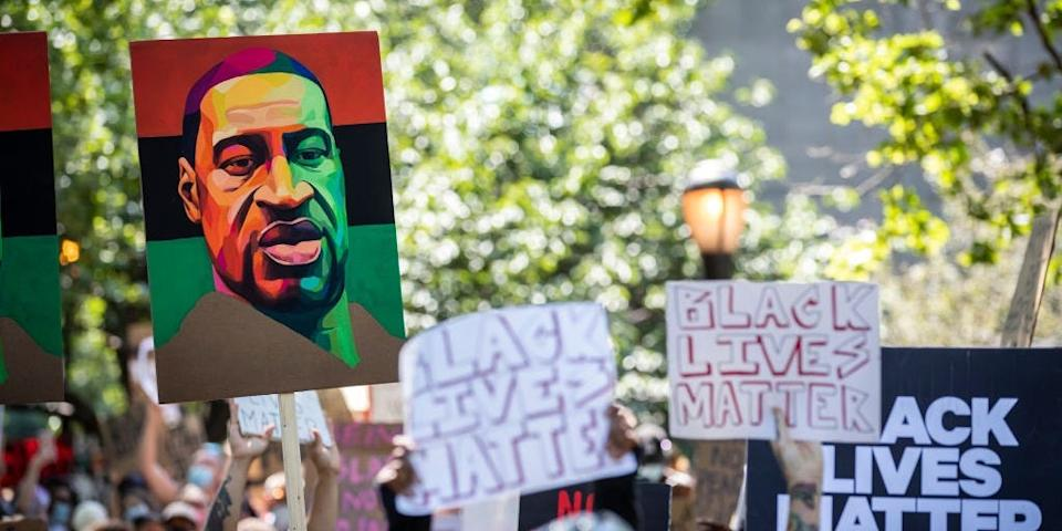"""Protesters hold signs that says, """"Black Lives Matter"""" a painted portraits of George Floyd with the Pan-African colors of Red, Black and Green behind them as they walk with thousands of protesters from Cadman Plaza to take part in the peaceful protest across the Brooklyn Bridge."""