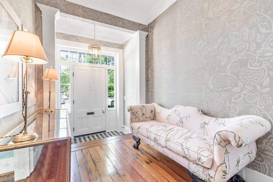<p>Sidelights and a transom let plenty of natural light pour into the foyer, where original hardwood take the spotlight.</p>