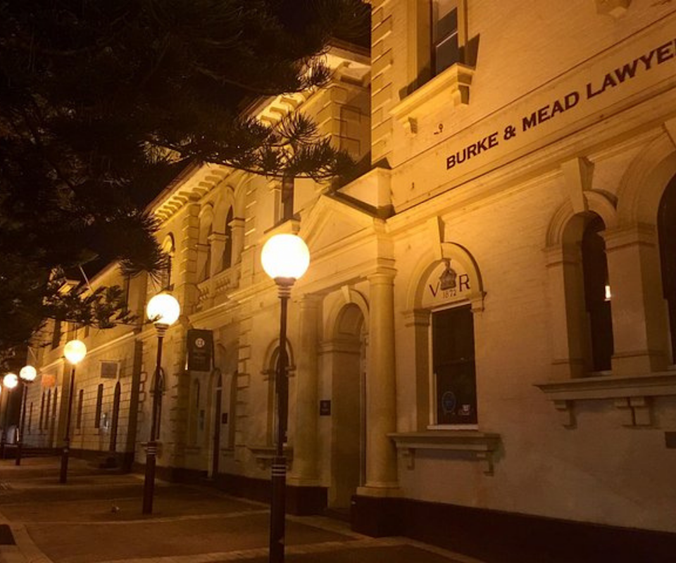 Image of a white heritage building in Newcastle at night lit by street lamps.