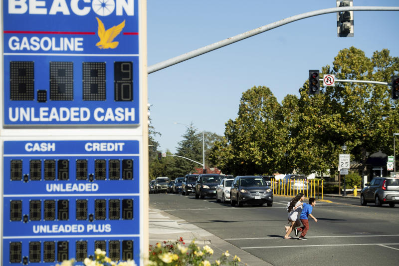 A gas station marquee and traffic lights remain dark as children cross Highway 12 during a power outage in Boyes Hot Springs, Calif., on Wednesday, Oct. 9, 2019. Pacific Gas and Electric has cut power to more than half a million customers in Northern California hoping to prevent wildfires during dry, windy weather throughout the region. (AP Photo/Noah Berger)