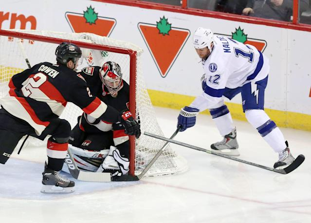 Tampa Bay Lighting's Ryan Malone (12) attempts a wrap around shot as Ottawa Senators goaltender Craig Anderson (41) and Jared Cownan (2) cover the net during the the first period of an NHL hockey game, Thursday, Jan. 30, 2014 in Ottawa, Ontario. (AP Photo/The Canadian Press, Fred Chartrand)