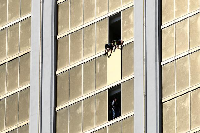 Workers board up a broken window at the Mandalay Bay hotel on Oct. 6, where Stephen Paddock killed 58 people and wounded more than 500 in Las Vegas days before. (Photo: Chris Wattie/Reuters)