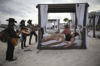 """Roving musicians """"Los Compas"""" serenade a couple on the shore of Mamitas beach, in Playa del Carmen, Quintana Roo state, Mexico, Tuesday, Jan. 5, 2021. Mexico saw a holiday bump in tourism amid the new coronavirus pandemic surge. (AP Photo/Emilio Espejel)"""