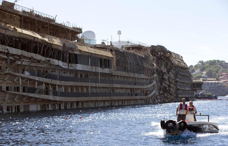 People take a small boat past the damaged side of he Costa Concordia on the Tuscan Island of Giglio, Italy, Wednesday, Sept. 18, 2013. The crippled cruise ship was pulled completely upright early Tuesday after a complicated, 19-hour operation to wrench it from its side where it capsized last year off Tuscany. (AP Photo/Andrew Medichini)