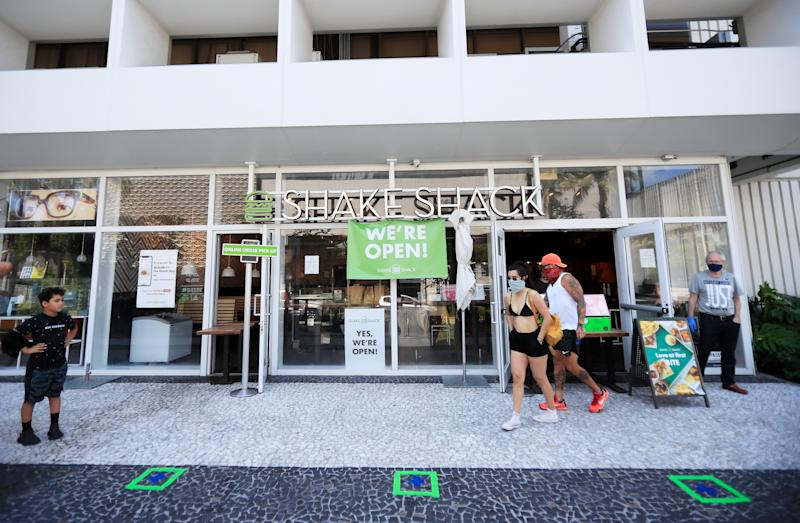 MIAMI BEACH, FLORIDA - APRIL 19: Customers wait for to-go orders outside Shake Shack in South Beach on April 19, 2020 in Miami Beach, Florida. Miami Beach restaurants are restricted to take-away and delivery orders due to the COVID-19 Pandemic. (Photo by Cliff Hawkins/Getty Images)