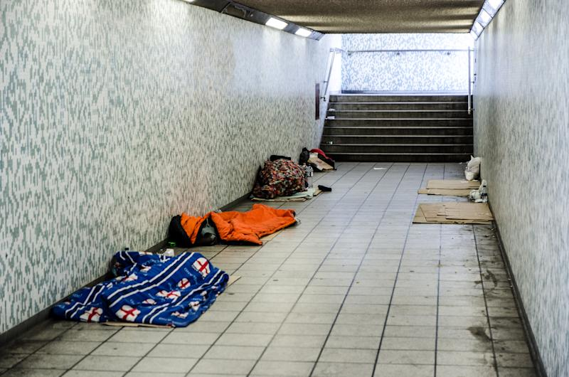 London, England - May 1, 2016: Three homeless people sleeping in sleeping bag in a tunnel with other empty spot marked with cardboards