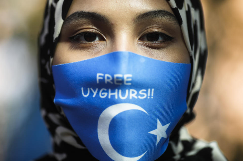 A woman wears a face mask reading 'Free Uyghurs' as she attends a protest during the visit of Chinese Foreign Minister Wang Yi in Berlin, Germany, Tuesday, Sept. 1, 2020. German Foreign Minister Heiko Maas meets his Chinese counterpart at the foreign ministry guest house Villa Borsig for bilateral talks. (AP Photo/Markus Schreiber)