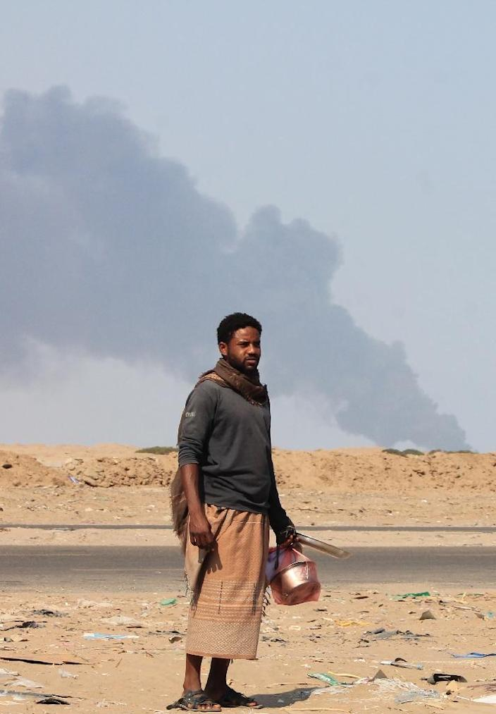 A Yemeni man carries kitchen utensils as he walks on a main road with smoke rising in the background from a strike allegedly targeting Huthi rebels on the outskirts in Yemen's second city of Aden on March 30, 2015 (AFP Photo/Saleh al-Obeidi)