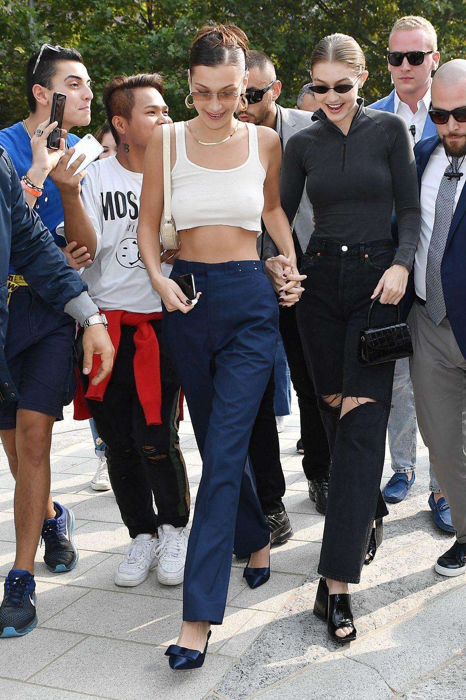 """<p>In a cropped white tank top, navy trousers, and navy <a href=""""https://senso.com.au/products/quebec-i-midnight"""" rel=""""nofollow noopener"""" target=""""_blank"""" data-ylk=""""slk:kitten heel pumps by Senso"""" class=""""link rapid-noclick-resp"""">kitten heel pumps by Senso</a> while out with sister Gigi Hadid in Milan.</p>"""