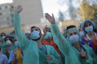 Health workers applaud as people react from their houses in support of the medical staff that are working on the COVID-19 virus outbreak at the Gregorio Maranon hospital in Madrid, Spain, Wednesday, April 1, 2020. The new coronavirus causes mild or moderate symptoms for most people, but for some, especially older adults and people with existing health problems, it can cause more severe illness or death. (AP Photo/Manu Fernandez)