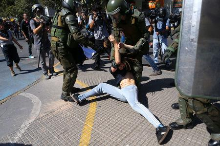 A demonstrator is detained by riot policemen during a protest calling for changes in the education system in Santiago