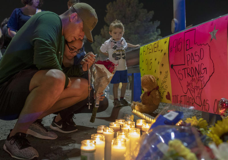 Rene Aguilar and Jackie Flores pray at a makeshift memorial for the victims of Saturday's mass shooting at a shopping complex in El Paso, Texas, Sunday, Aug. 4, 2019. (AP Photo/Andres Leighton)