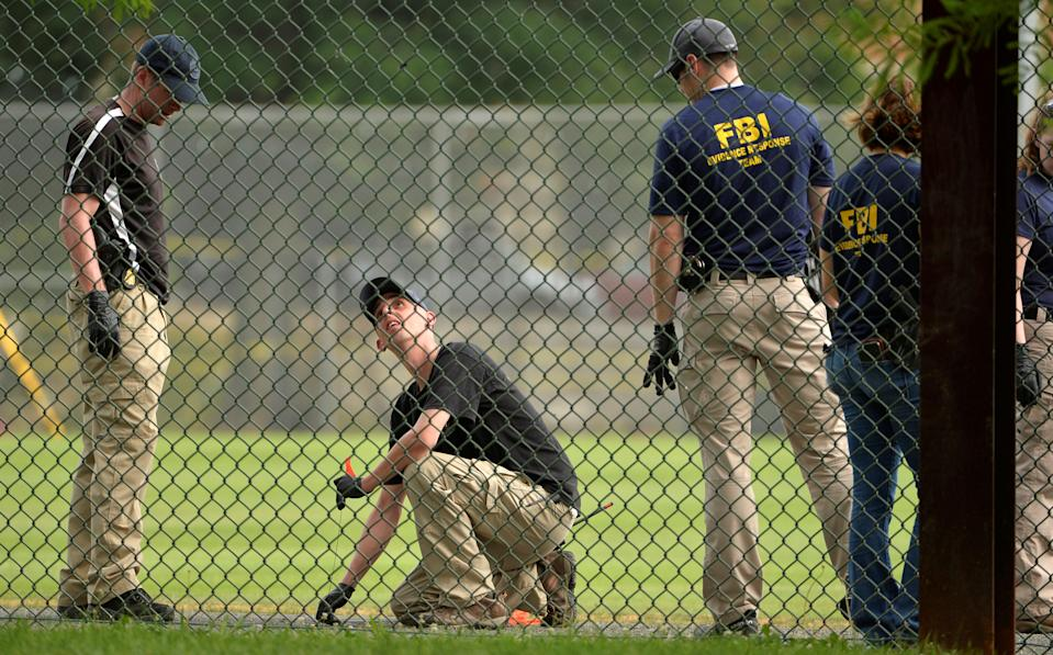 FBI technicians examine a baseball field where shots were fired during a congressional baseball practice in Alexandria, Va., June 14, 2017. (Mike Theiler/Reuters)