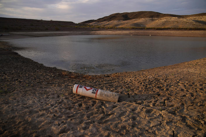 FILE - In this Aug. 13, 2021, file photo a buoy rests on the ground at a closed boat ramp on Lake Mead at the Lake Mead National Recreation Area near Boulder City, Nev. The U.S. Bureau of Reclamation released projections Wednesday, Sept. 22, 2021, that indicate an even more troubling outlook for a river that serves millions of people in the U.S. West. The agency recently declared the first-ever shortage on the Colorado River, which means Arizona, Nevada and Mexico won't get all the water they were allocated next year. (AP Photo/John Locher, File)