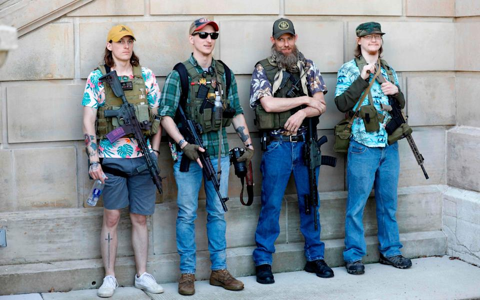 "In this file photo taken on May 20, 2020 Armed protesters demonstrate during the Michigan Conservative Coalition organized ""Operation Haircut"" outside the Michigan State Capitol in Lansing, Michigan. Under their bulletproof vests and assault rifles, all four wear brightly-coloured Hawaiian shirts - Jeff Kowalsky/AFP"