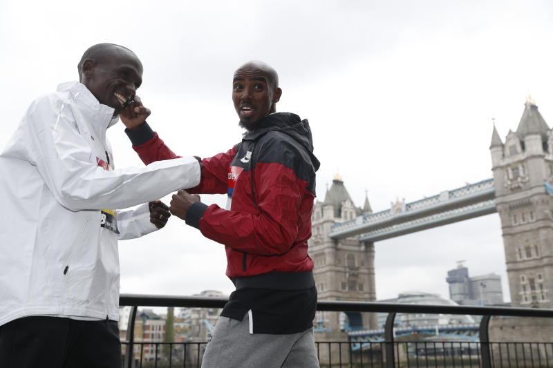 Britain's Mo Farah, right, and Kenya's Eliud Kipchoge pose for the media during a photo call for the London Marathon in London, Wednesday, April 24, 2019. Kipchoge and Farah are part of the Elite Men taking part in the 39th London Marathon which takes place Sunday April 28. (AP Photo/Alastair Grant)