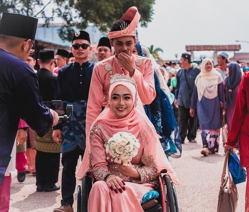 Amirul Syahmi Mohd Yazid with his wheelchair bound wife Siti Aishah Zaid at a marriage solemnisation event. – Picture via Facebook