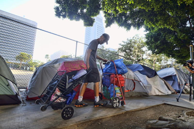 FILE - In this July 1, 2019 file photo, a homeless man moves his belongings from a street near Los Angeles City Hall, background, as crews prepared to clean the area. The Los Angeles Homeless Services Authority has failed to meet goals for placing people into permanent housing and for referring them to substance abuse and mental health treatment, according to a city audit released Wednesday, Aug. 28, 2019. (AP Photo/Richard Vogel, File)