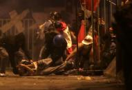 FILE PHOTO: A demonstrator is injured on the ground as he is help by other demontrators during a clash with police during a protest against the decision of Congress to remove former President Martin Vizcarra, in Lima
