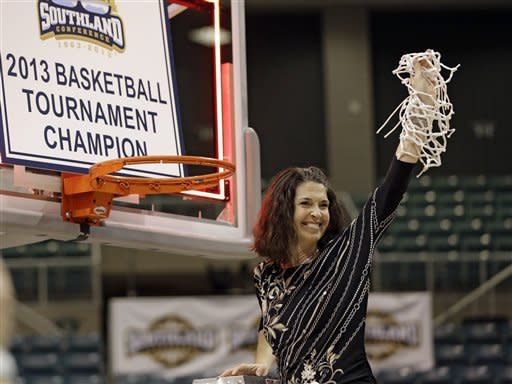Oral Roberts coach Misti Cussen holds up the net while after winning the Southland Conference championship basketball game against Sam Houston, Saturday, March 16, 2013, in Katy, Texas. Oral Roberts defeated Sam Houston 72-66. (AP Photo/David J. Phillip)