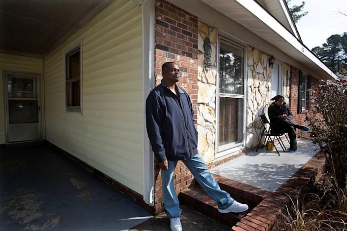 """Henry McCollum, 50, spends time outdoors with his sister, Geraldine Brown, 49, rear, in Fayetteville, N.C. """"I'm happy to be out here breathing the cool air,"""" he says. He and his brother Leon Brown, 47, not seen, both served 31 years for a rape and murder of a young girl which they did not commit. They were freed in September 2014. Both are happy to out of prison, but find that it's been a hard adjustment on the outside. They have no income and no car, which makes it difficult to find work and earn money."""